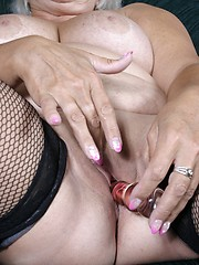 Busty granny in fishnets toying her shaved pussy