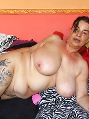 Tattoed granny moves fingers on own smooth hole