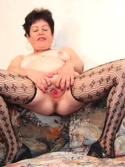 Dark-haired mature grabs her shaved vagina by some toys